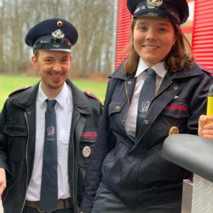 Feuerwehrmann und Feuerwehrfrau in Uniform mit Feuerwehr-Krawatten